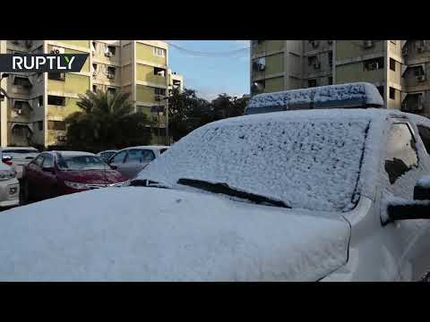 شاهد الثلوج تغطي الأشجار والسيارات وأسطح المباني في شوارع بغداد