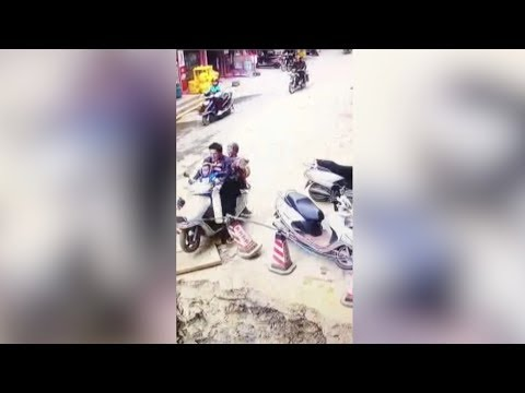 man drives motorcycle carrying family