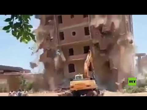 شاهد لحظة انهيار عقار كبير على حفارة أثناء إزالته في مصر